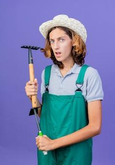 真面目な顔でミニ熊手を保持しているジャンプスーツと帽子を身に着けている若い庭師の男