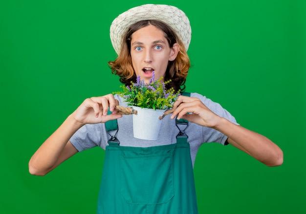 鉢植えの植物を保持しているジャンプスーツと帽子を身に着けている若い庭師の男は驚いた