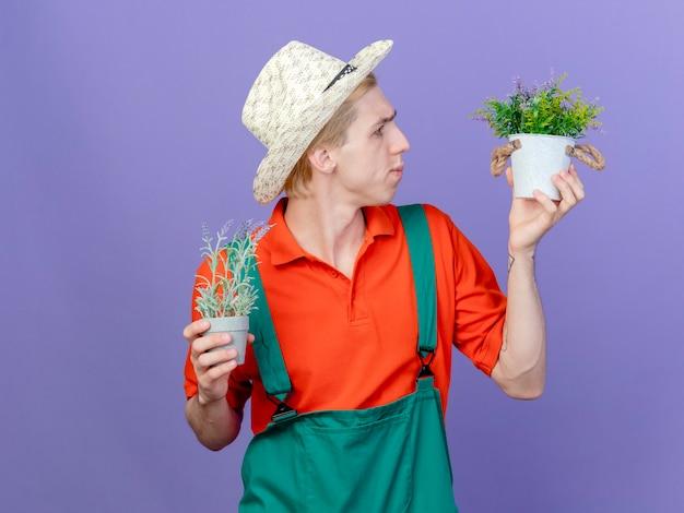 Молодой садовник в комбинезоне и шляпе с горшечными растениями
