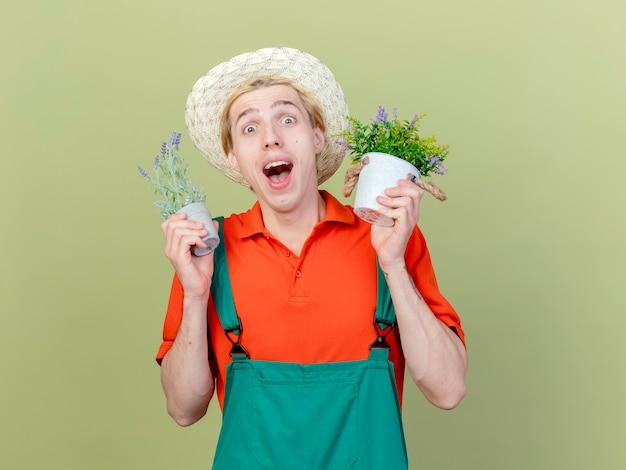 鉢植えの植物を保持しているジャンプスーツと帽子を身に着けている若い庭師の男