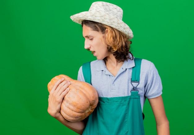 カボチャを保持しているジャンプスーツと帽子を身に着けている若い庭師の男