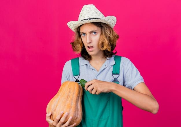 호박과 오이를 들고 죄수 복과 모자를 쓰고 젊은 정원사 남자