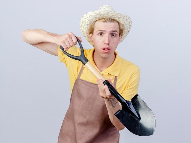 Молодой садовник в комбинезоне и шляпе с лопатой в замешательстве