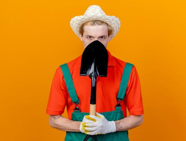 Молодой садовник в комбинезоне и шляпе держит лопату и смотрит в камеру, пряча лицо на оранжевом фоне