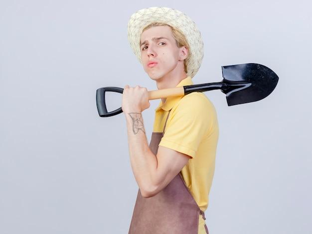 Молодой садовник в комбинезоне и шляпе, держащий лопату на плече, выглядит уверенно