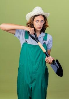 シャベルを保持しているジャンプスーツと帽子を身に着けている若い庭師の男