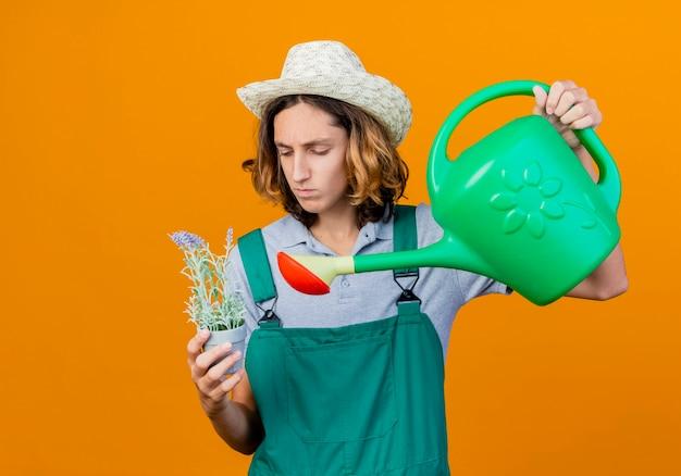 물을 수와 화분을 들고 죄수 복과 모자를 쓰고 젊은 정원사 남자
