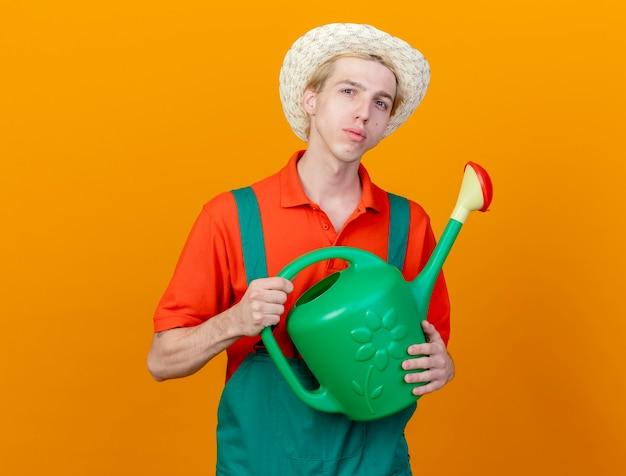 じょうろを保持しているジャンプスーツと帽子を身に着けている若い庭師の男は、オレンジ色の背景の上に立っている深刻な顔でカメラを見ることができます