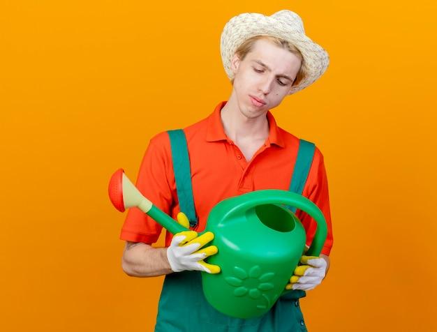 じょうろを持ってジャンプスーツと帽子をかぶった若い庭師の男は、オレンジ色の背景の上に立っている深刻な顔でそれを見ることができます