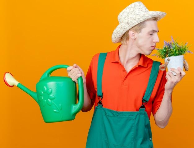 죄수 복과 물을 들고 모자를 입고 젊은 정원사 남자 수 있습니다.