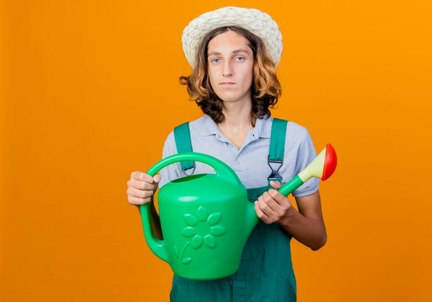 じょうろを保持しているジャンプスーツと帽子を身に着けている若い庭師の男