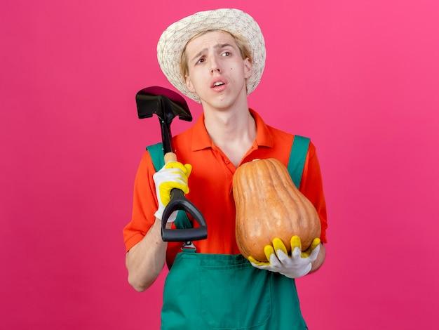 シャベルを保持しているゴム手袋でジャンプスーツと帽子を身に着けている若い庭師の男
