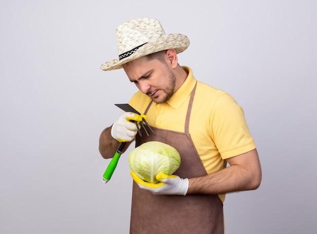 真面目な顔で見ているキャベツとマトックを保持している作業用手袋でジャンプスーツと帽子を身に着けている若い庭師の男