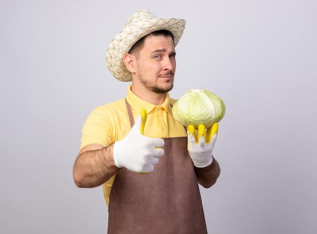 親指を立ててカメラでキャベツlookignを保持している作業手袋でジャンプスーツと帽子を身に着けている若い庭師の男