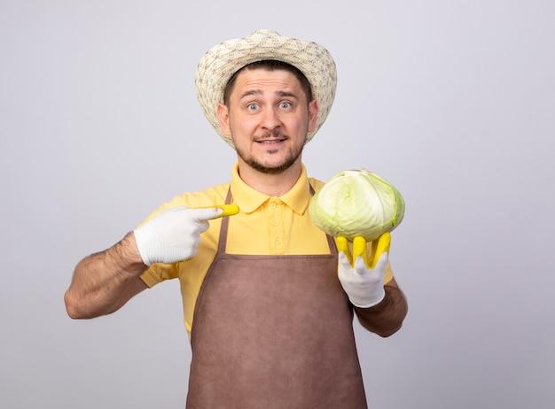 作業用手袋にジャンプスーツと帽子をかぶった若い庭師の男