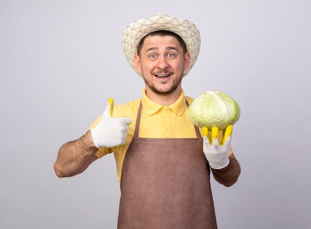 幸せそうな顔で笑顔のキャベツを保持している作業手袋でジャンプスーツと帽子を身に着けている若い庭師の男