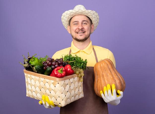 野菜とカボチャでいっぱいの箱を持って作業用手袋でジャンプスーツと帽子を身に着けている若い庭師の男は幸せで前向きに笑っています