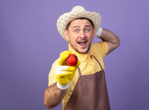 Молодой садовник в комбинезоне и шляпе в рабочих перчатках держит свежий помидор и радостно улыбается