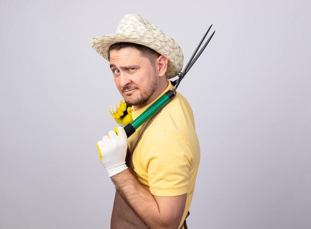 젊은 정원사 남자는 카메라에 자신감을 미소 헤지 클리퍼 lookign 들고 작업 장갑에 죄수 복과 모자를 입고