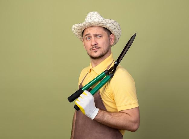 Молодой садовник в комбинезоне и шляпе в рабочих перчатках держит ножницы для живой изгороди с уверенным выражением лица