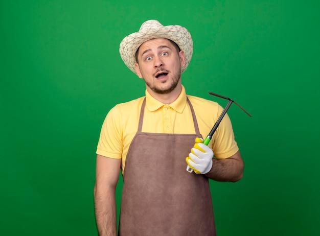 混乱しているマトックを保持している作業用手袋でジャンプスーツと帽子を身に着けている若い庭師の男