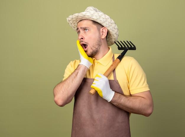 미니 갈퀴를 들고 작업 장갑에 죄수 복과 모자를 쓰고 젊은 정원사 남자가 빛 벽 위에 서서 놀랍고 놀라게했습니다.