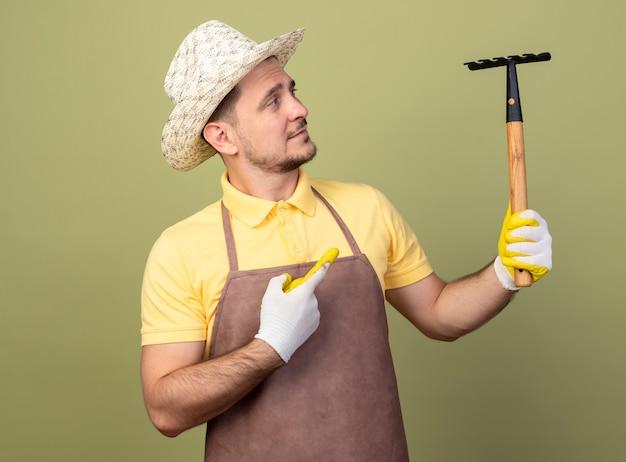 빛 벽 위에 자신감이 서 미소 그것에 검지 손가락으로 가리키는 미니 갈퀴를 들고 작업 장갑에 죄수 복과 모자를 입고 젊은 정원사 남자