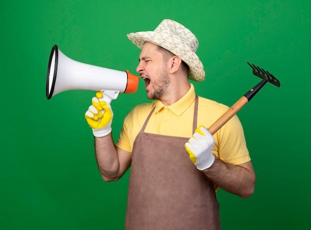 攻撃的な表情でメガホンに叫んでミニ熊手を保持している作業用手袋でジャンプスーツと帽子を身に着けている若い庭師の男