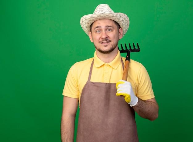 陽気な笑顔のミニ熊手を保持している作業用手袋でジャンプスーツと帽子を身に着けている若い庭師の男