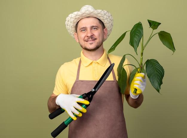 식물과 울타리 가위를 들고 작업 장갑에 죄수 복과 모자를 쓰고 젊은 정원사 남자가 빛 벽 위에 서있는 얼굴에 미소로 정면을보고 있습니다.