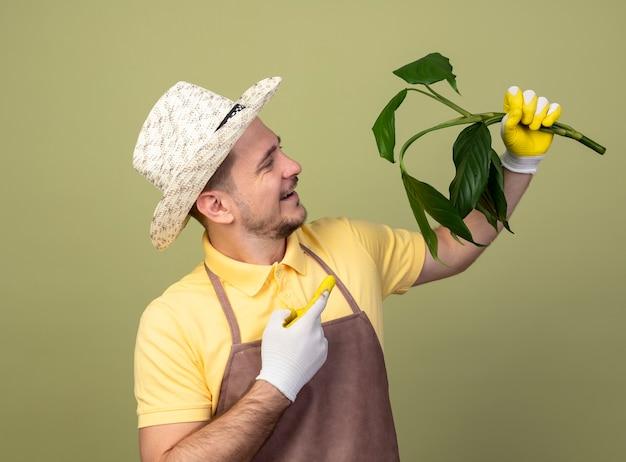 집게 손가락으로 가리키는 식물을 들고 작업 장갑에 죄수 복과 모자를 쓰고 젊은 정원사 남자가 빛 벽 위에 유쾌하게 서서 웃고 있습니다.