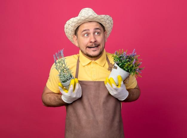 混乱している脇を見ている鉢植えの植物を保持している作業用手袋でジャンプスーツと帽子を身に着けている若い庭師の男