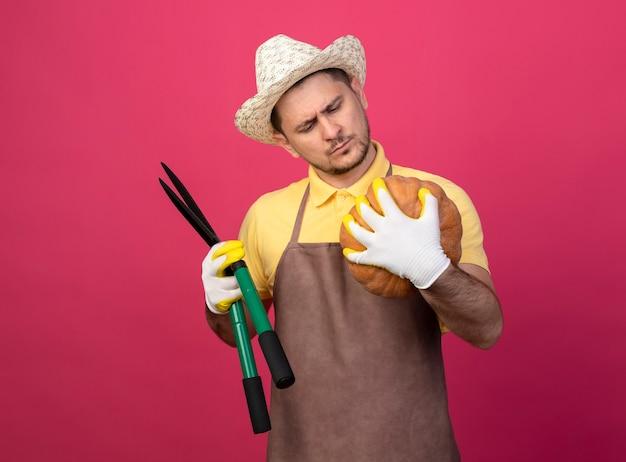 カボチャを保持している作業用手袋でジャンプスーツと帽子を身に着けている若い庭師の男