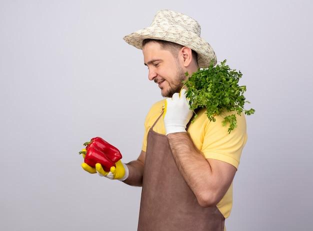 Молодой садовник в комбинезоне и шляпе в рабочих перчатках держит красный перец и свежие травы, смотрит с улыбкой на лице