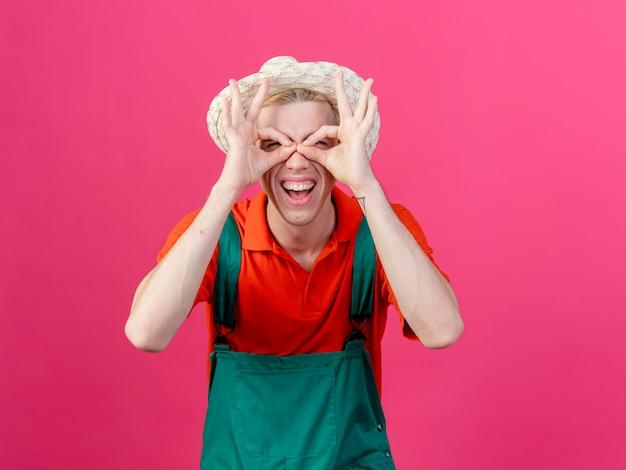 ピンクの背景の上に立って双眼ジェスチャーを作る指を通してカメラを見てジャンプスーツと帽子を身に着けている若い庭師の男