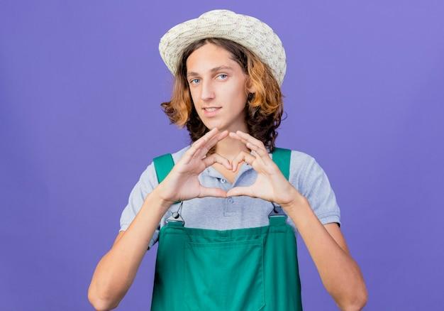 ジャンプスーツと帽子をかぶって若い庭師の男が笑顔でハートジェスチャーを作る