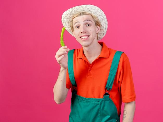 녹색 칠리 페 퍼를 보여주는 죄수 복과 모자를 쓰고 젊은 정원사 남자
