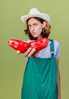 Молодой садовник в комбинезоне и шляпе с красным перцем