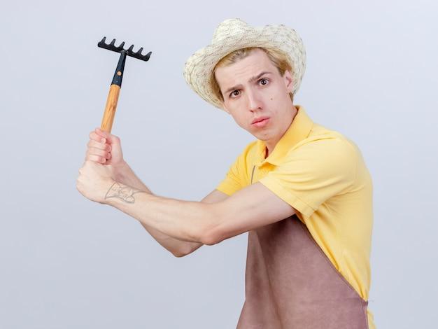 ジャンプスーツと帽子をかぶった若い庭師の男が不機嫌なミニ熊手を振る