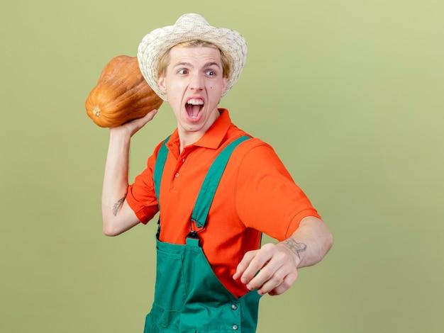 明るい背景の上に立って攻撃的な表情で叫んでジャンプスーツと帽子を振るカボチャを身に着けている若い庭師の男