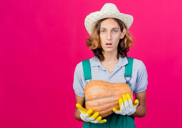 カボチャを保持しているゴム手袋を着用してジャンプスーツと帽子を身に着けている若い庭師の男
