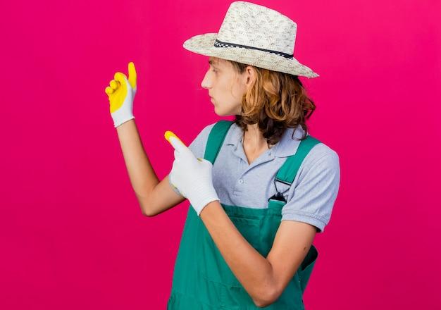 つなぎ服とゴム手袋をはめて帽子をかぶった若い庭師