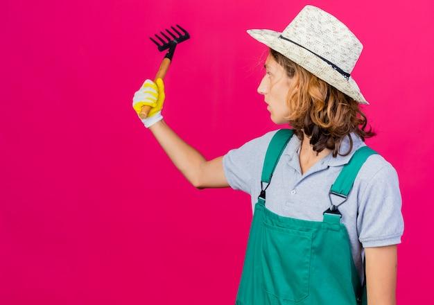 ゴム手袋を着用してジャンプスーツと帽子を身に着けている若い庭師の男