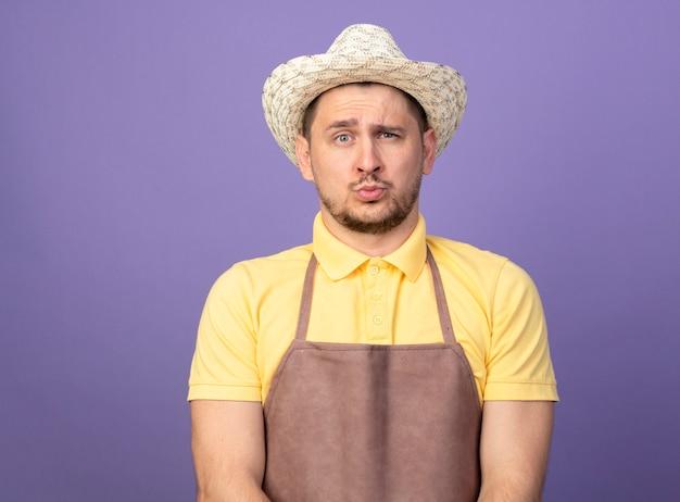自信を持って表情でジャンプスーツと帽子をかぶっている若い庭師の男