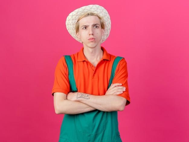 Молодой садовник в комбинезоне и шляпе с серьезным лицом со скрещенными руками на груди