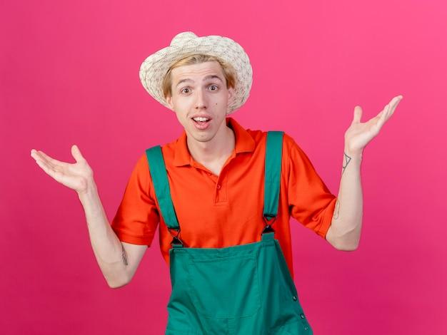 Giovane giardiniere uomo che indossa tuta e cappello confuso diffondendo le mani ai lati