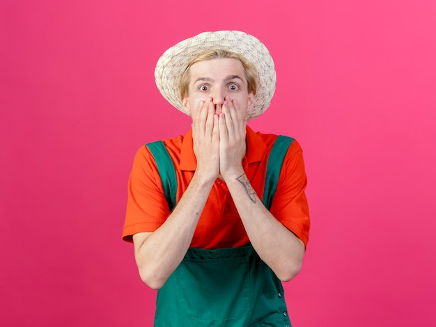Young gardener man wearing jumpsuit and hat being shocked covering mouth with hands