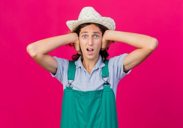 Giovane giardiniere uomo che indossa tuta e cappello che copre le orecchie con le mani