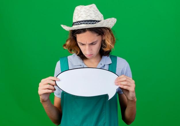 Giovane giardiniere uomo che indossa tuta e cappello che tiene il segno in bianco del fumetto