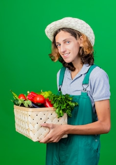 Young gardener man wearing jumpsuit and hat holding crate full of fresh vegetables